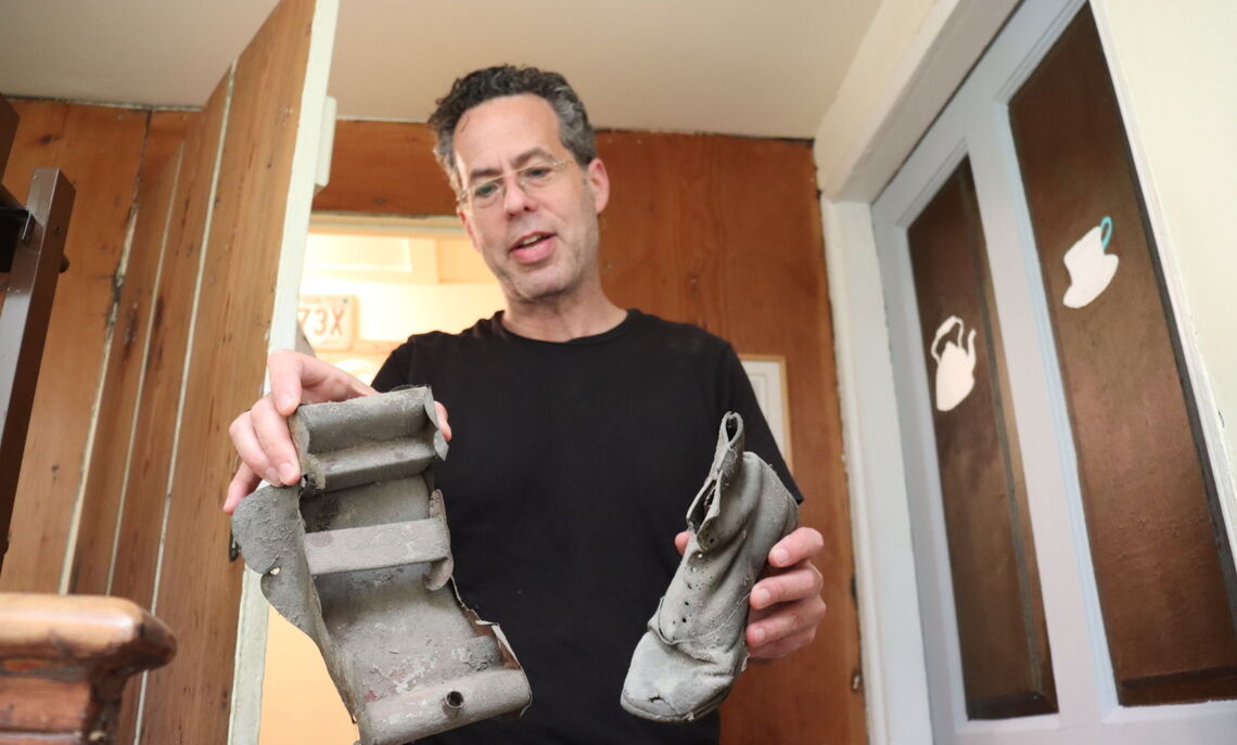 A homeowner of an 1812 house on Gaskill Street shows the students some of the belongings of immigrants a century ago, a shoe and toy sled unearthed in their attic.