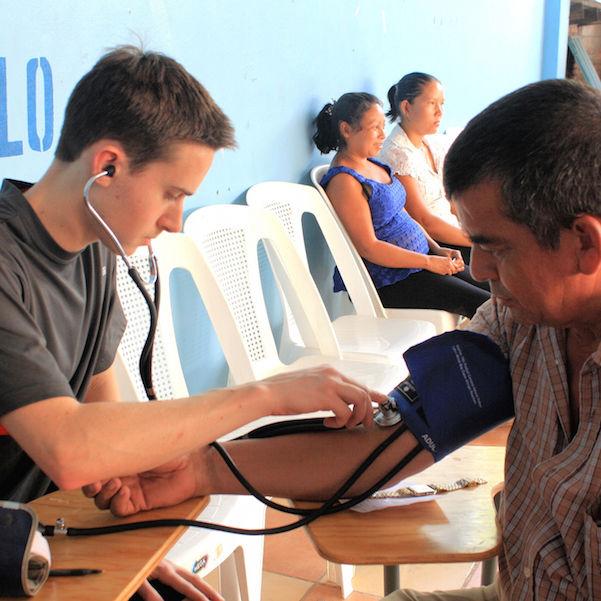 Ryan Von Kleek '15 takes blood pressure for a patient at a clinic in Honduras during the Honduras Alternative Spring Break.