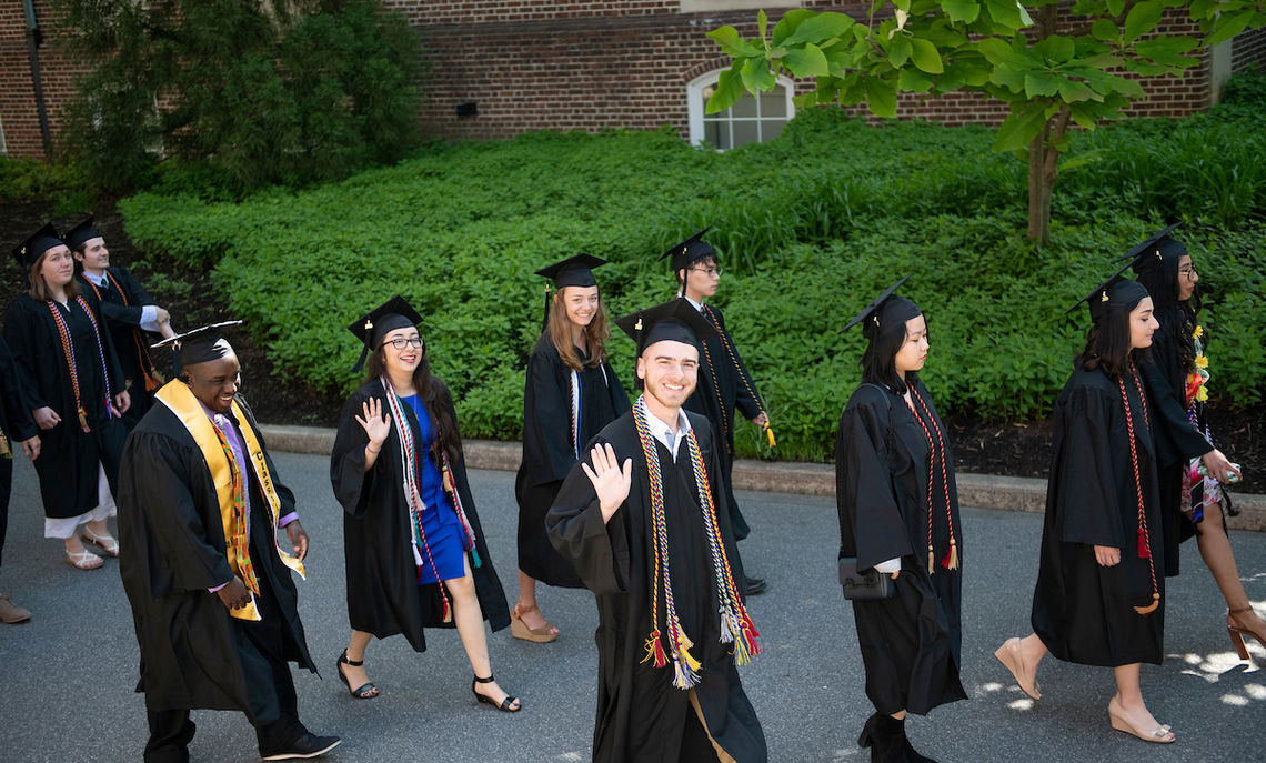 Graduates begin the procession to Commencement ceremonies on Hartman Green.