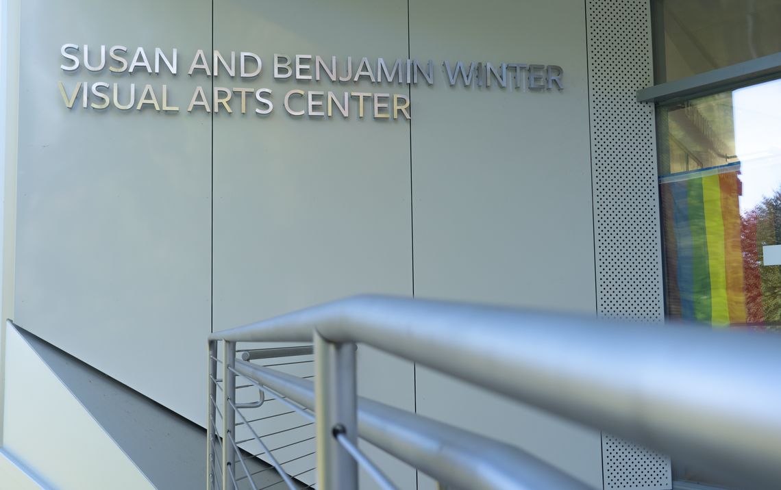 """The ramp entrance to Winter Visual Arts Center. """"Susan and Benjamin Visual Arts Center"""" is written on the wall in silver. In the window next to the glass doors, a gay pride flag is visible."""