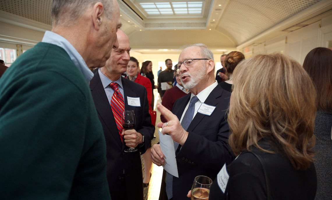 Professor Joe Karlesky shares a point with alumni Stan Brand.