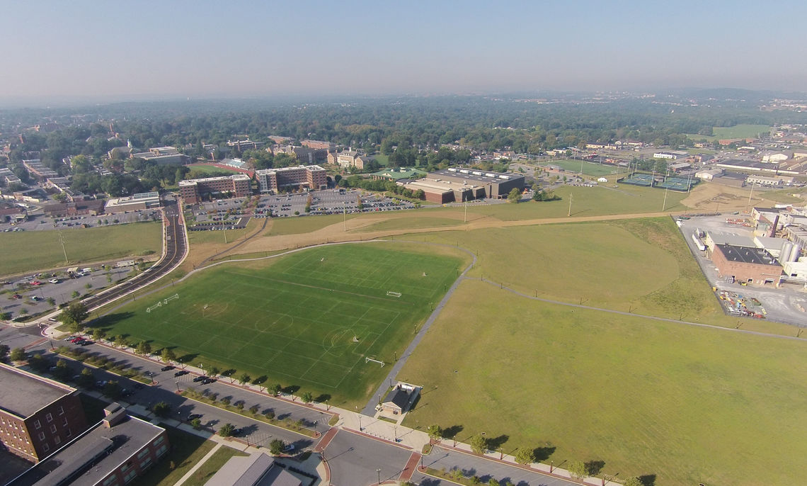 2015: Looking south, green fields will one day become F&M's comprehensive athletics pre- cinct. Armstrong's brick buildings used to be on the right, while a new roadway on the left now connects College Avenue and Liberty Street.