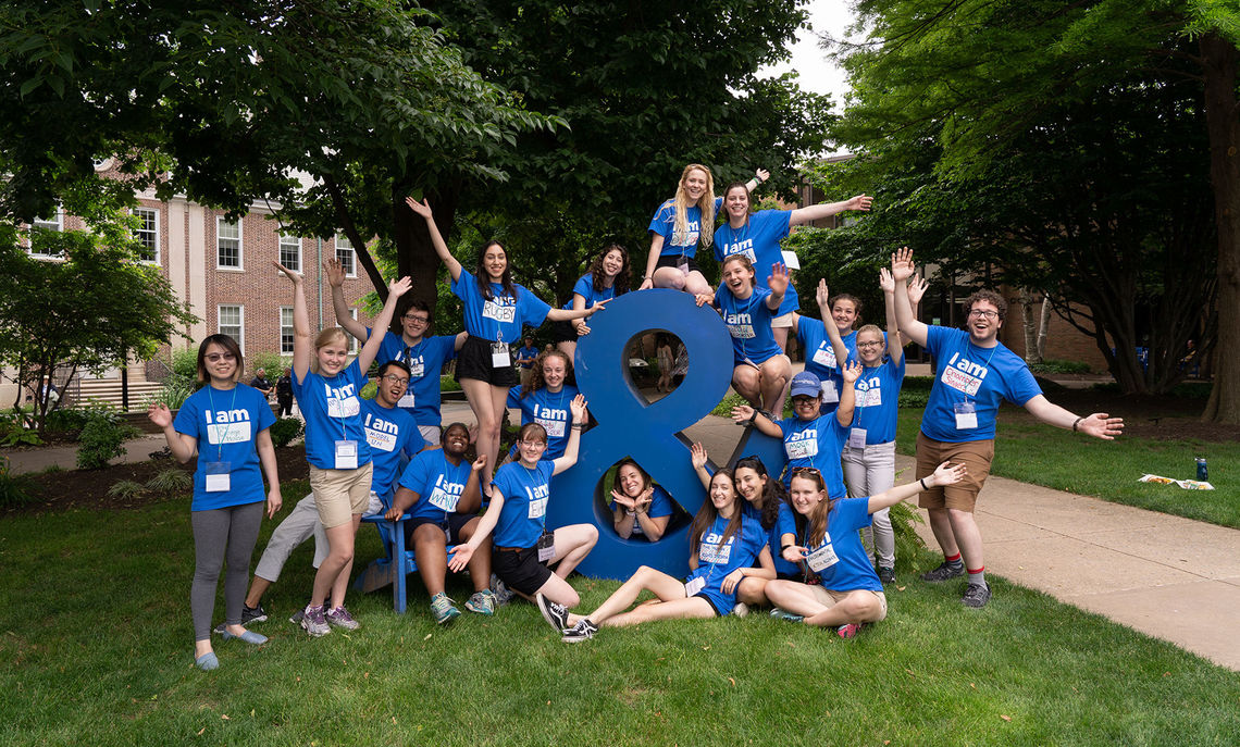 Student ambassadors gather around Andy the Ampersand in their identifiable blue T-shirts.