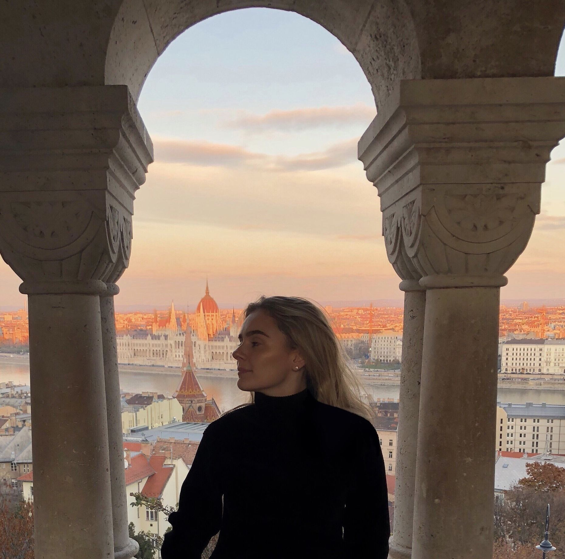 A photo of Elisjana in front of an expansive view of a city.