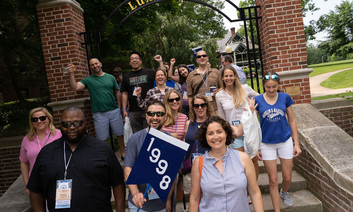 Members of the Class of 1998 pose in front of the 'Lux et Lex' arch, celebrating their 20th reunion.