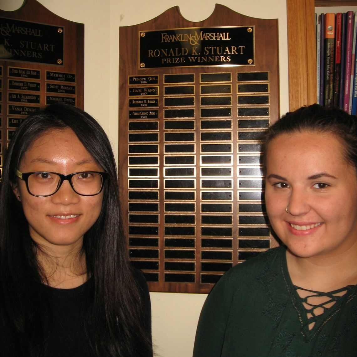From left, Chengcheng Zhai '18 and Katherine M. Kidder '18 stand near the Stuart Memorial Prize plaque, which hangs in the Math Department Common Room, Stager Hall 211. The prize is awarded each year to the senior or seniors who accomplish the best mathematical work of all students in the graduating class.