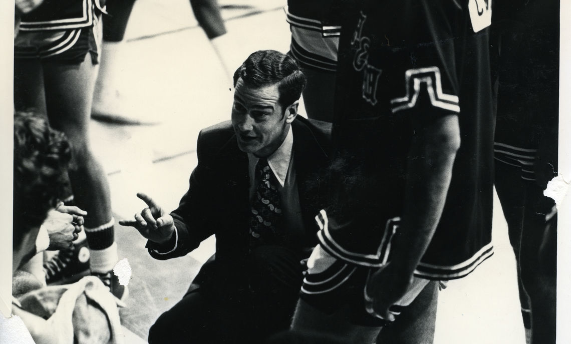 The coach at work in earlier days, addressing his team in the huddle.