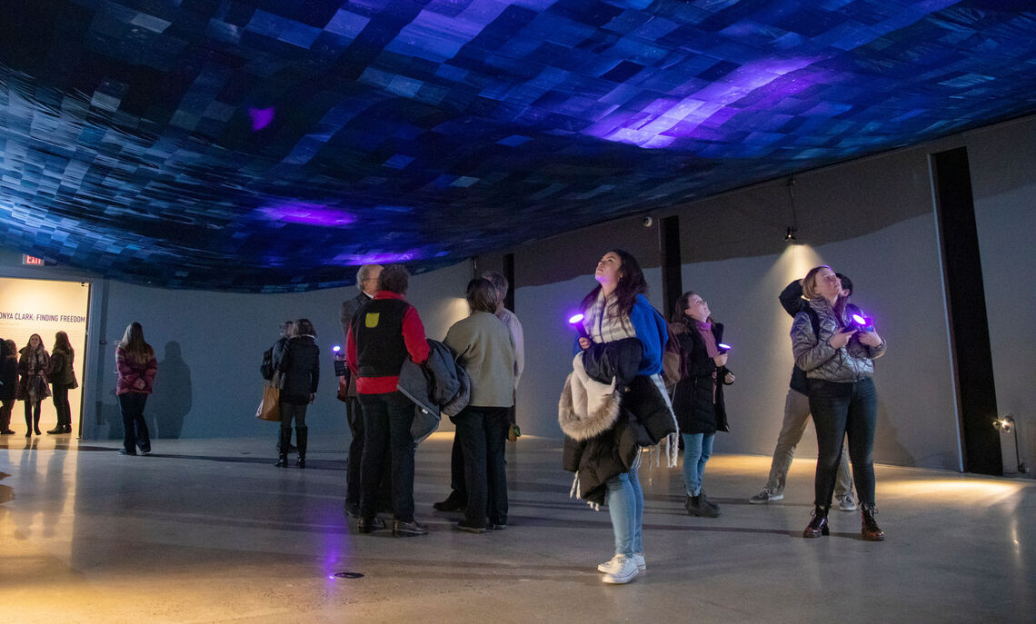 """Visitors activating Sonya Clark's """"Finding Freedom"""" with black lights at the opening reception of the exhibition. Photo by Deb Grove."""