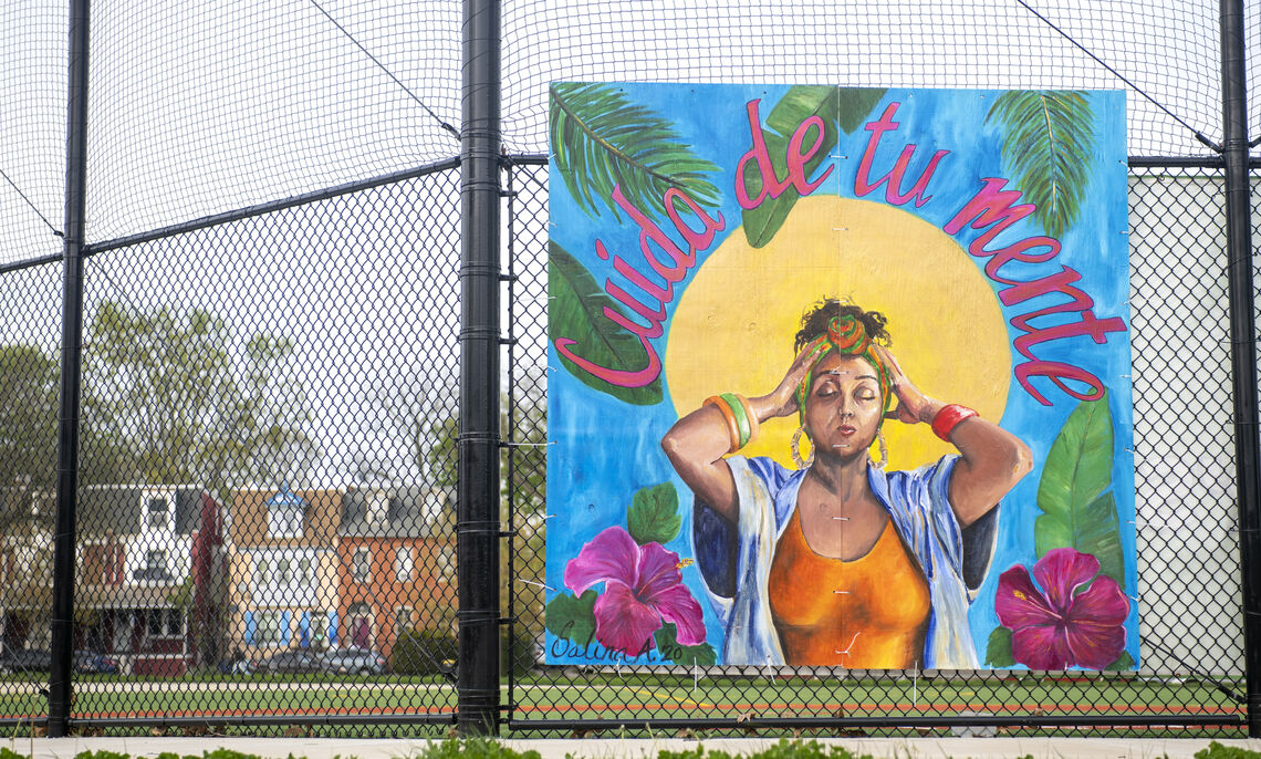 Peter Barber and Salina Almanzar install a painted mural at Roberto Clemente field in Lancaster as part of a city-wide arts project conveying public health messaging related to COVID-19.
