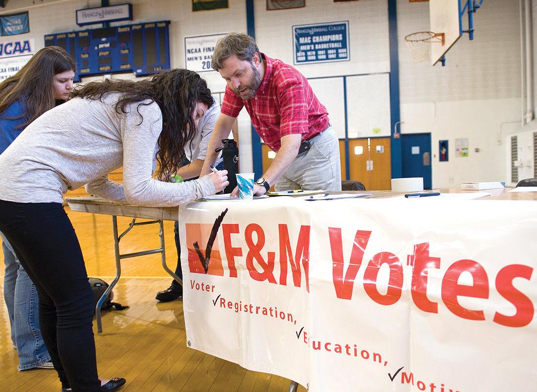 Assistant Professor of Biology Pablo Jenik helps students fill out voter- registration forms Sept. 20 in Mayser Gymnasium.