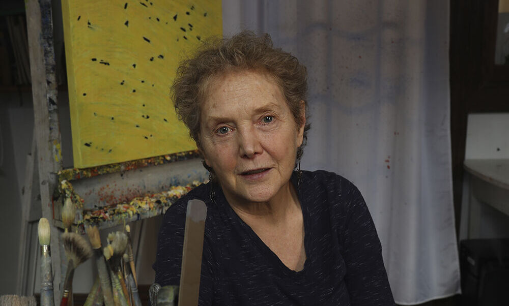 A photo of artist Francie Lyshak sitting with art supplies in front of her at a table and a recent yellow and black abstract painting behind her.