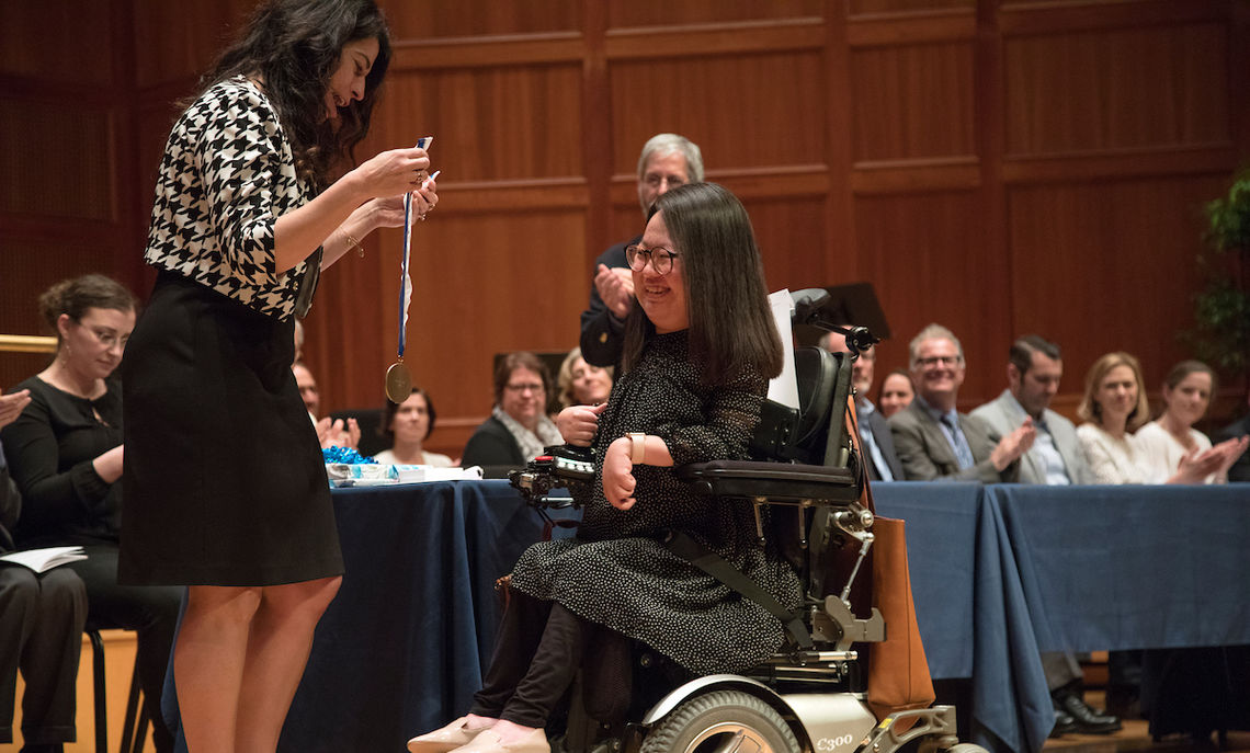 F&M Senior Associate Dean of the College Maria d. Flores-Mills presents Hye Rin Lee '18,  recipient of this year's Major Dick Winters '41 Award, with the medal.