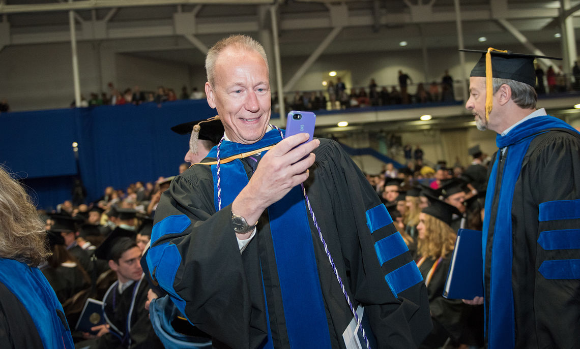 Dean Hammer, The John W. Wetzel Professor of Classics and Professor of Government and don of New College House, captures a photo of some graduating seniors.