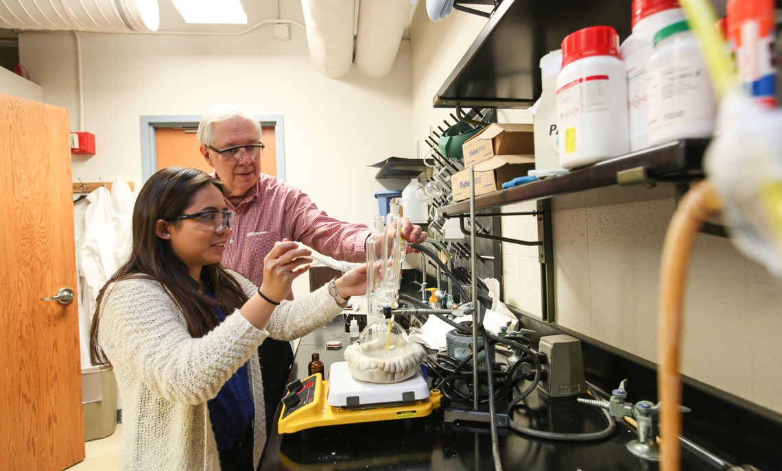 Charles A. Dana Professor of Chemistry Claude Yoder working on research with junior Linh Tran, a chemistry major, one of the many students he has mentored over his nearly 50 years of teaching.