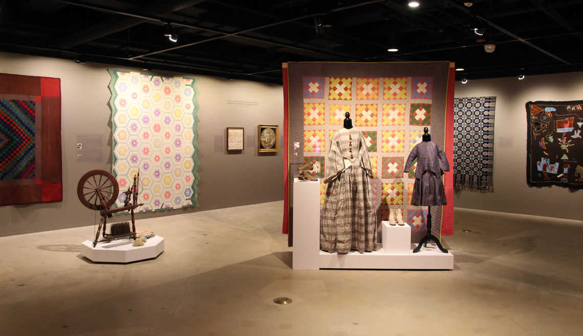 Photograph of the exhibition Stitched Stories that reexamined textiles found in the Phillips Museum of Art's permanent collection, crafted by women from the 19th through the 20th centuries