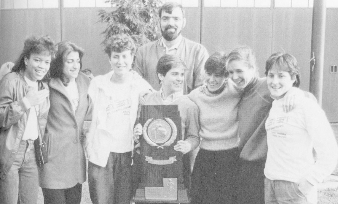The 1985 Division III National Champions in cross country (from left): Terry Smith, Lois Lucente, Laurie Reynolds, Katrina Harriman (holding the NCAA trophy), Amanda Shaw, Nancy Leet, and Dee Dee Hemingway. Coach Ed Woge stands behind his team. Lucente and Shaw earned All American honors.