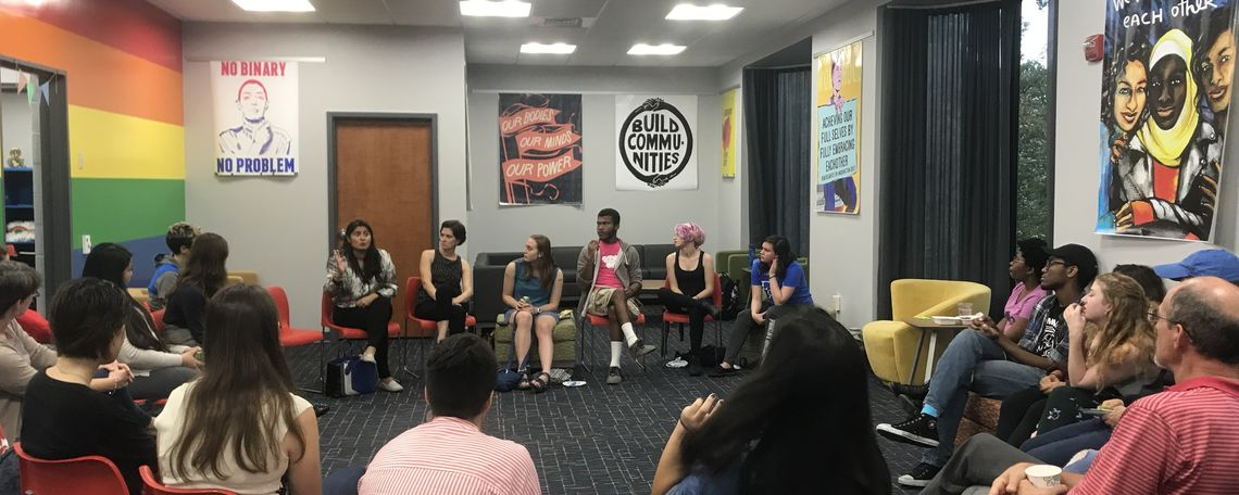 An image of the Alice Drum Women's center with students arranged in a circle in the midst of a discussion.