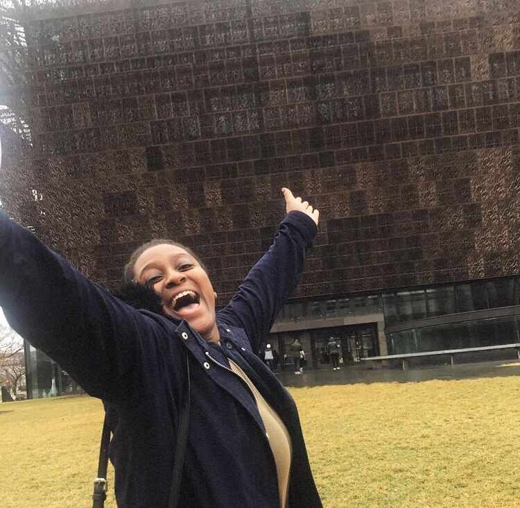 A photo of Shannon with her arms spread wide and smiling in front of the National Museum for African American History and Culture.