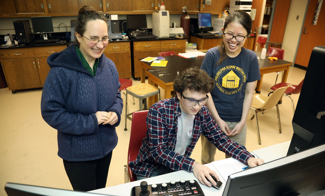 In this 2018 photo, Han Le and fellow chemistry major Angus Unruh  work with Professor Kate Plass on the latest computer microscope.