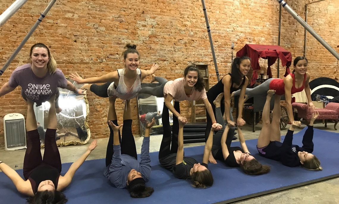 """Members of Dance Team went to the Circus school of Lancaster to learn partner acro and counter balancing. They are demonstrating the bird pose with one """"flyer"""" being lifted by the legs of the """"base.:"""