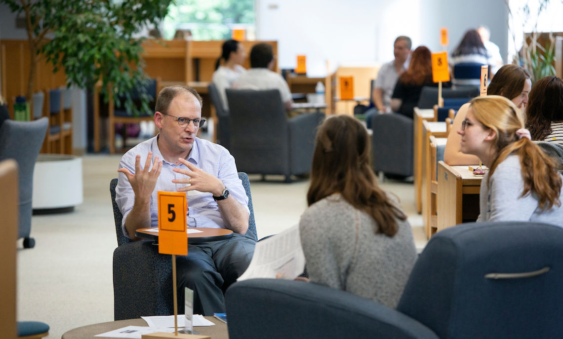 At the Human Library, where conversations that challenge stereotypes and prejudices through dialogue took place, Professor of Chemistry Ed Fenlon engages with two students.