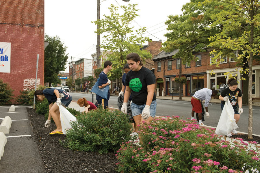 A group of F&M students spruces up a small garden near a parking lot on North Queen Street in downtown Lancaster.