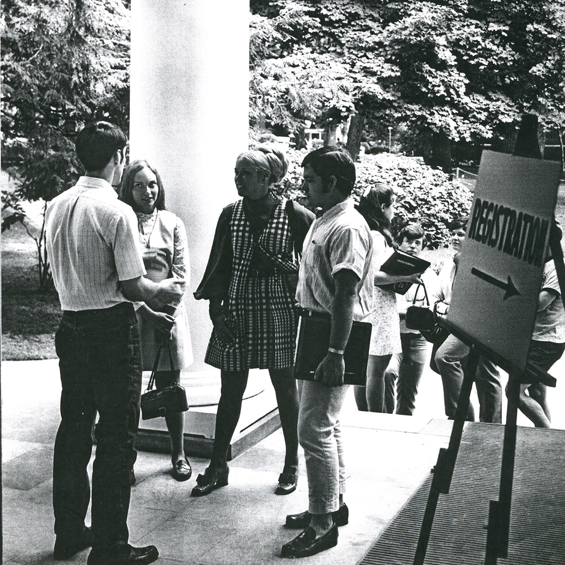 Group of students beside a sign for registration, 1969