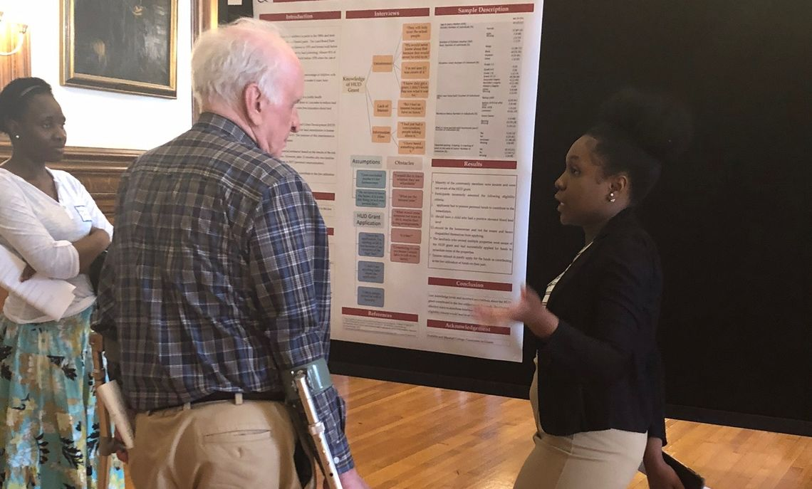 Najeda Regis shares her research findings on how well the public is informed about lead abatement programs with Dr. Robert Sharrar '62 as Professor Okatch listens.