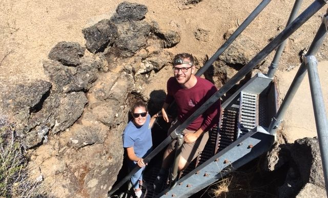 At the Golden Dome lava tube, senior geoscience majors Sam Patzkowksy and  Halle Putera prepare to descend below the earth.