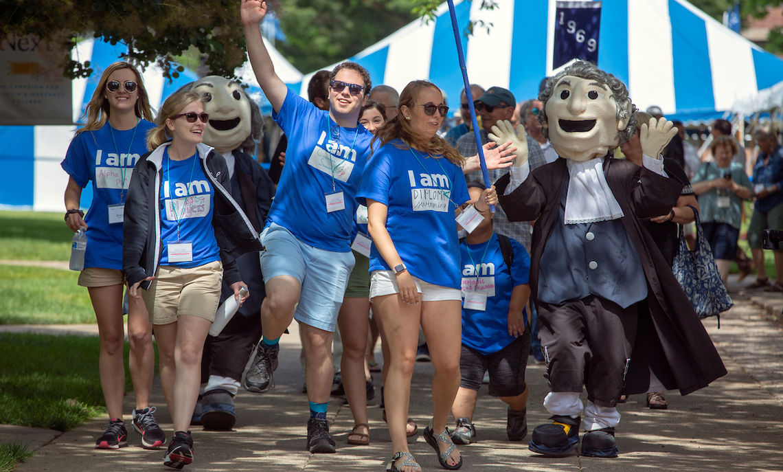 Student volunteers lead the Reunion Class Parade to Hensel Hall.