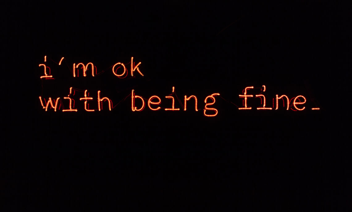 "Neon art by Stephanie Lifshutz '13 that reads, ""i'm ok with being fine"" in a serif font."