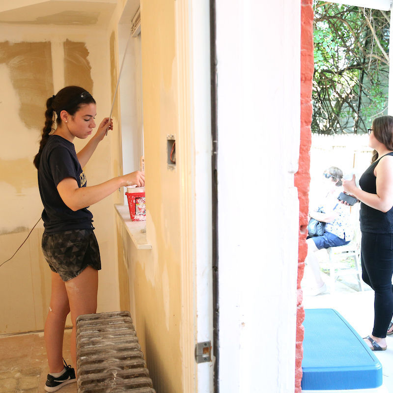 PSSI interns paint a house for Habitat for Humanity.
