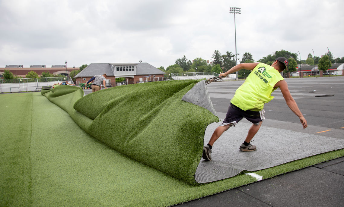 A crew installs new turf at Tylus Field, home of the Diplomats' field hockey and soccer teams.