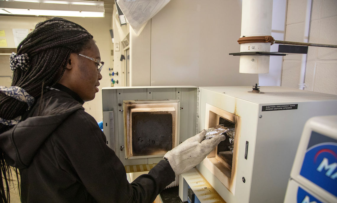 Hussein places the samples in an Earth & Environment furnace for burning.