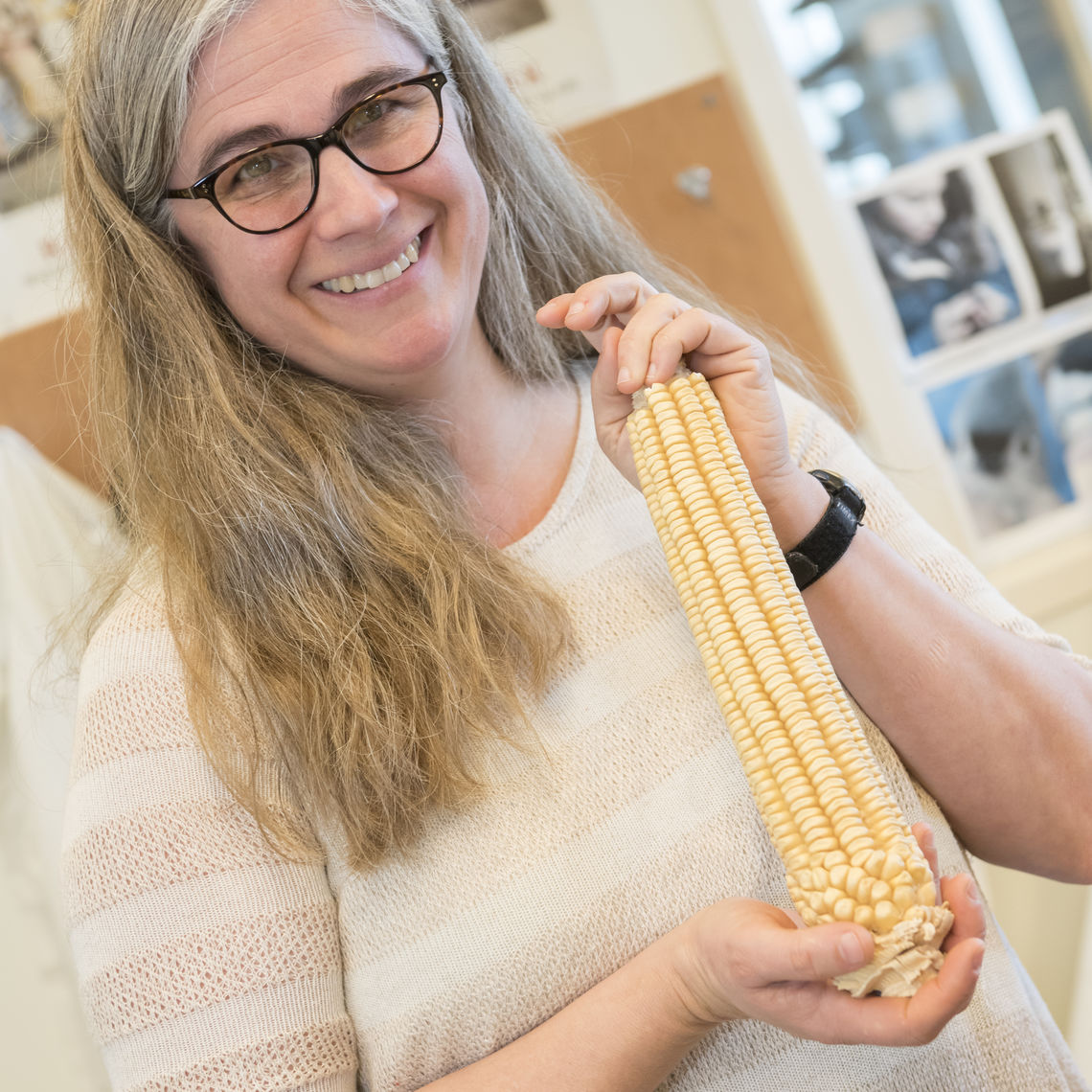 Ellie Rice's research interests include population genetics in the context of plant genetic diversity conservation. In a lab in the Barshinger Life Sciences & Philosophy Building, she displays an ear of corn—one of several she uses in her work on plant genetics.