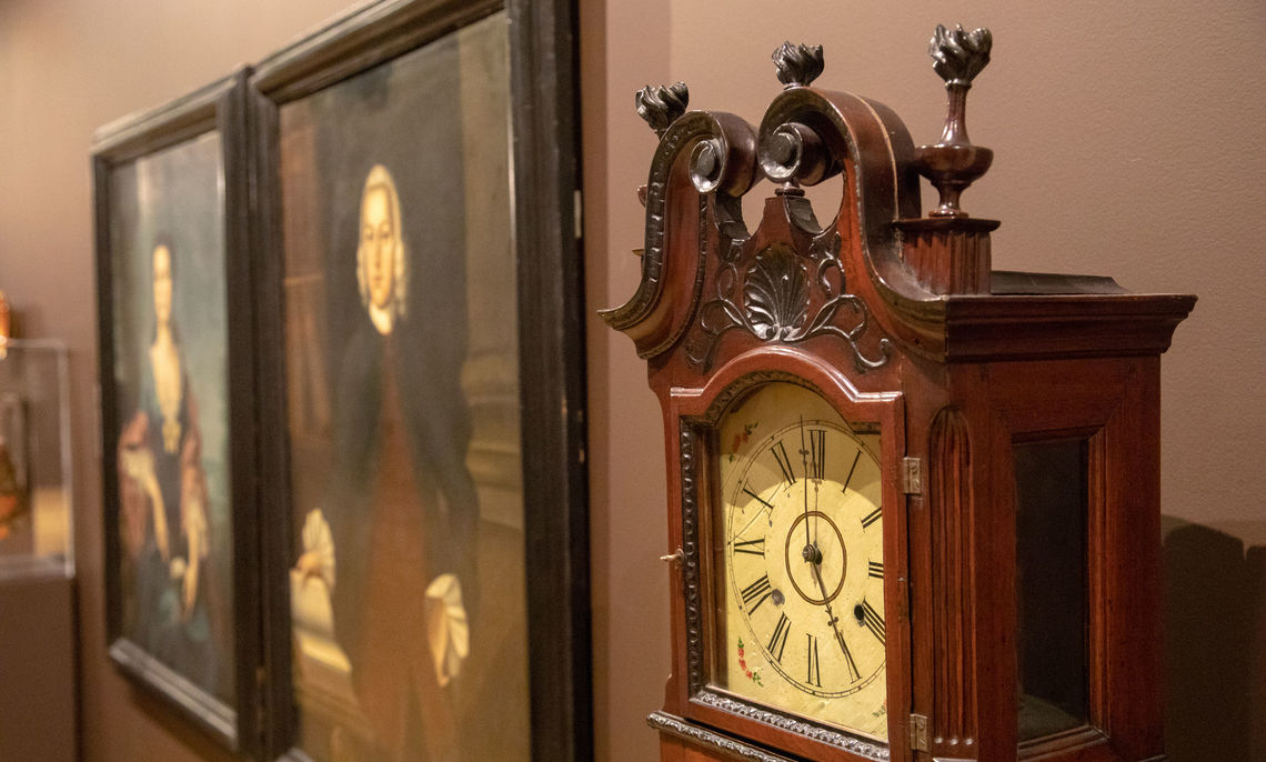 Photograph of a clock and two early portraits by Benjamin West from the Nisslery Gallery Fall 2018.