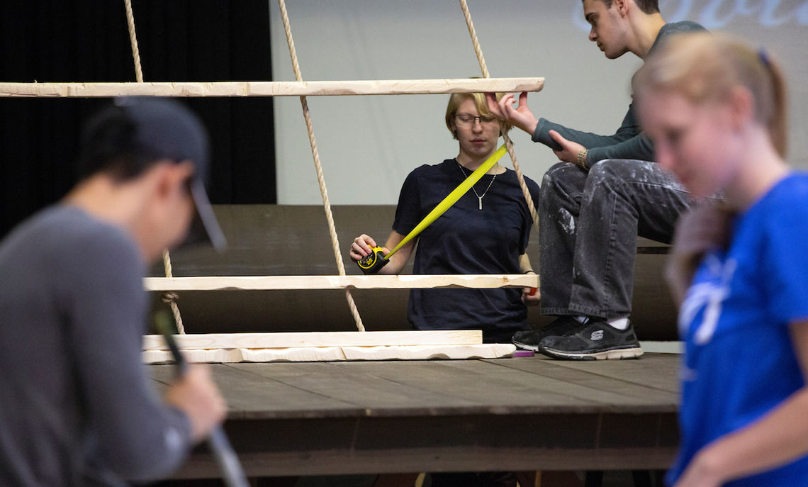 Students prepare the stage setting that includes a sailing ship and a penal colony.