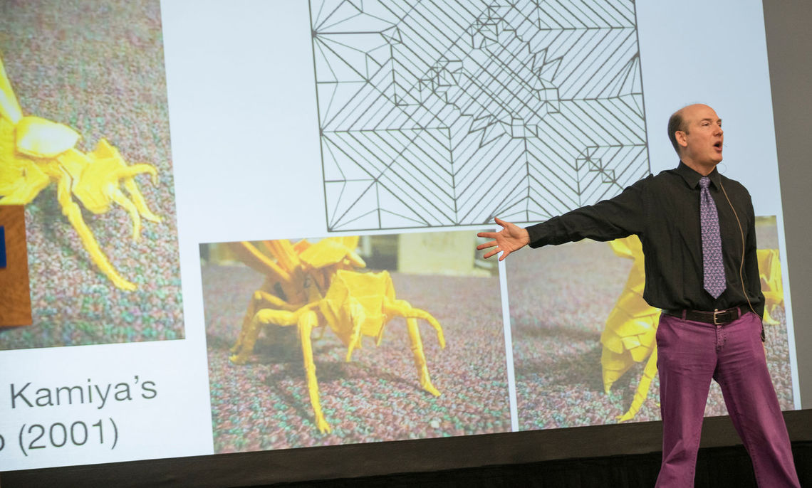 Common Hour speaker Dr. Thomas Hull points out the fine details and complex folding pattern of an origami insect.