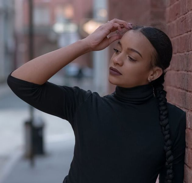 A photograph of Keyla wearing a black turtleneck and gray slacks and staring off into the distance.