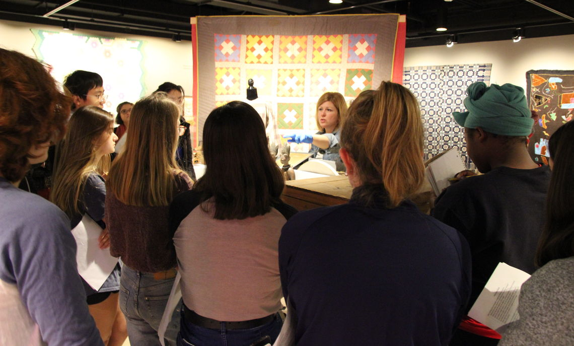 """Assistant Director and Collections Manager Lindsay Marino leads a discussion with Professor Guarasci's General Anthropology class in the exhibition """"Stitched Stories."""" Photo by Gina Erdyneeva '20."""