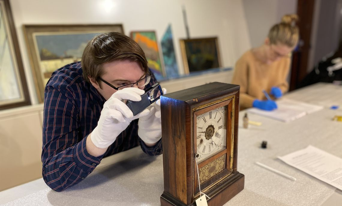 Student closely examining a clock from the museum's permanent collection as part of the course CNX 258, Object Lessons, taught by Professor Aleci. Photo by Gina Erdyneeva '20.