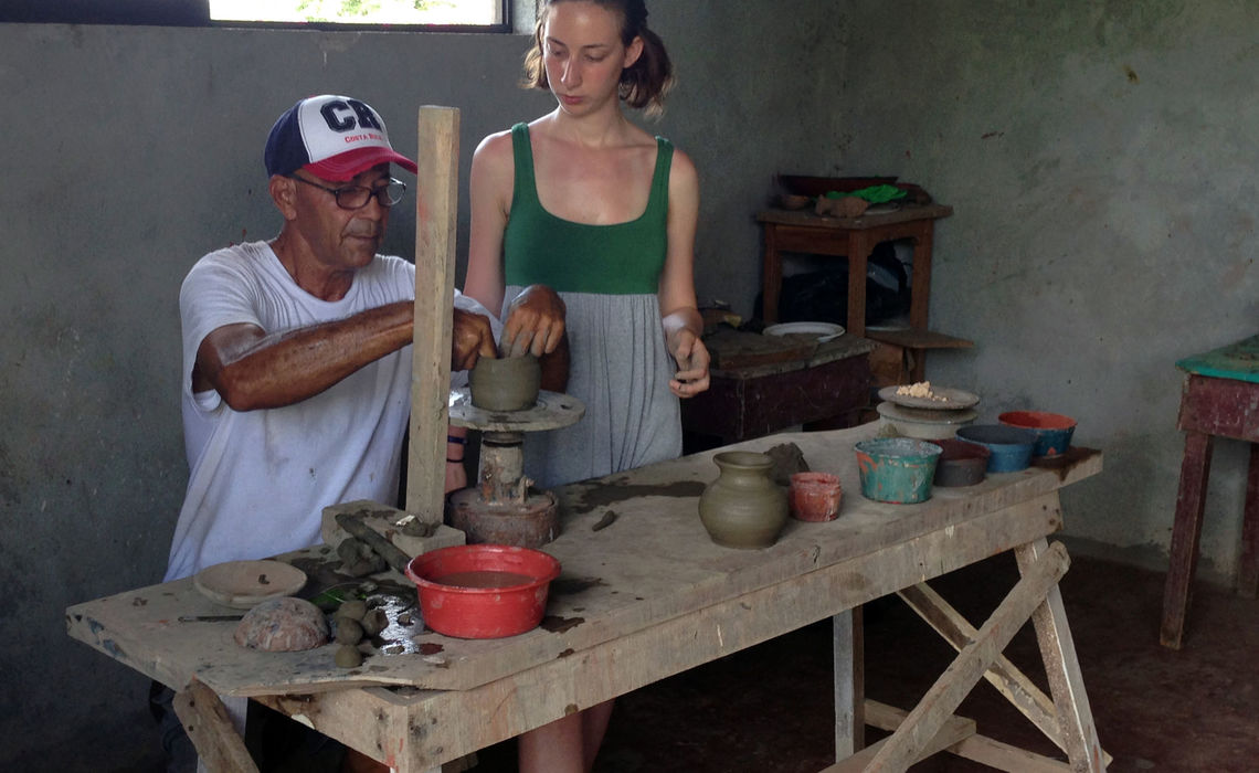 Trying her hand at traditional pottery, made with sand from the neck of an Iguana, junior Julia Fleisch gets tips from the local artisan.