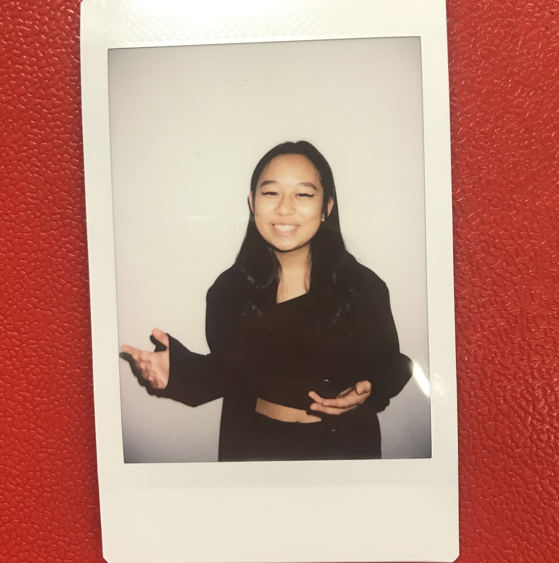 A Polaroid photo of Vi smiling at the camera.