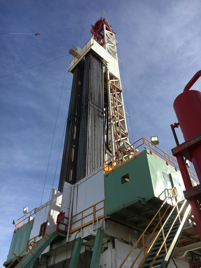 Pipes for oil drilling are hung in the rig.
