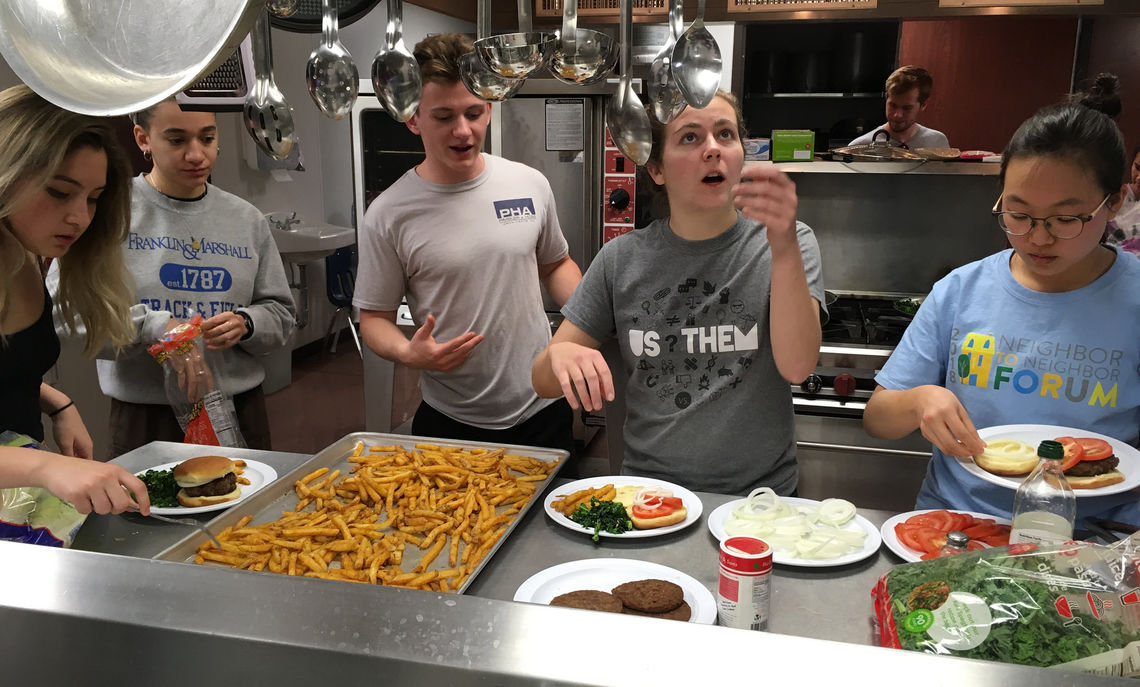 Junior Tyler Donaghy makes burgers and fries at the grill for (left to right) junior Soprina Guarneri, senior Karolina Heleno, junior Gabe Pimsler, junior Kate Myers, and senior Julie Byun.