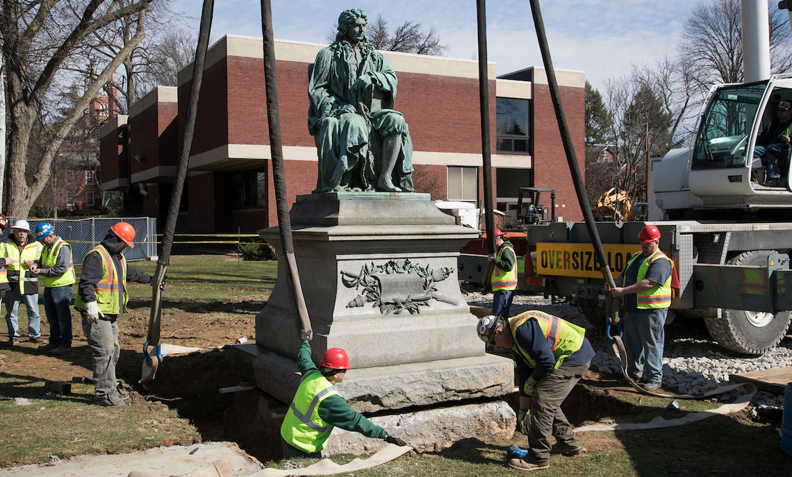 Crews get the crane's straps in place.