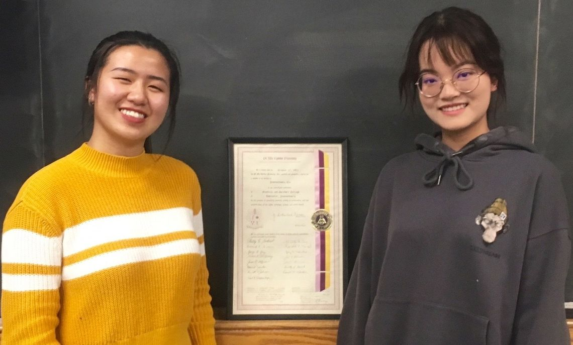 From left, Past President Yinxi Li '19 and newly-elected 2019-20 President Xinyang Chen '20 stand beside F&M's Pi Mu Epsilon original charter that dates back to 1969.