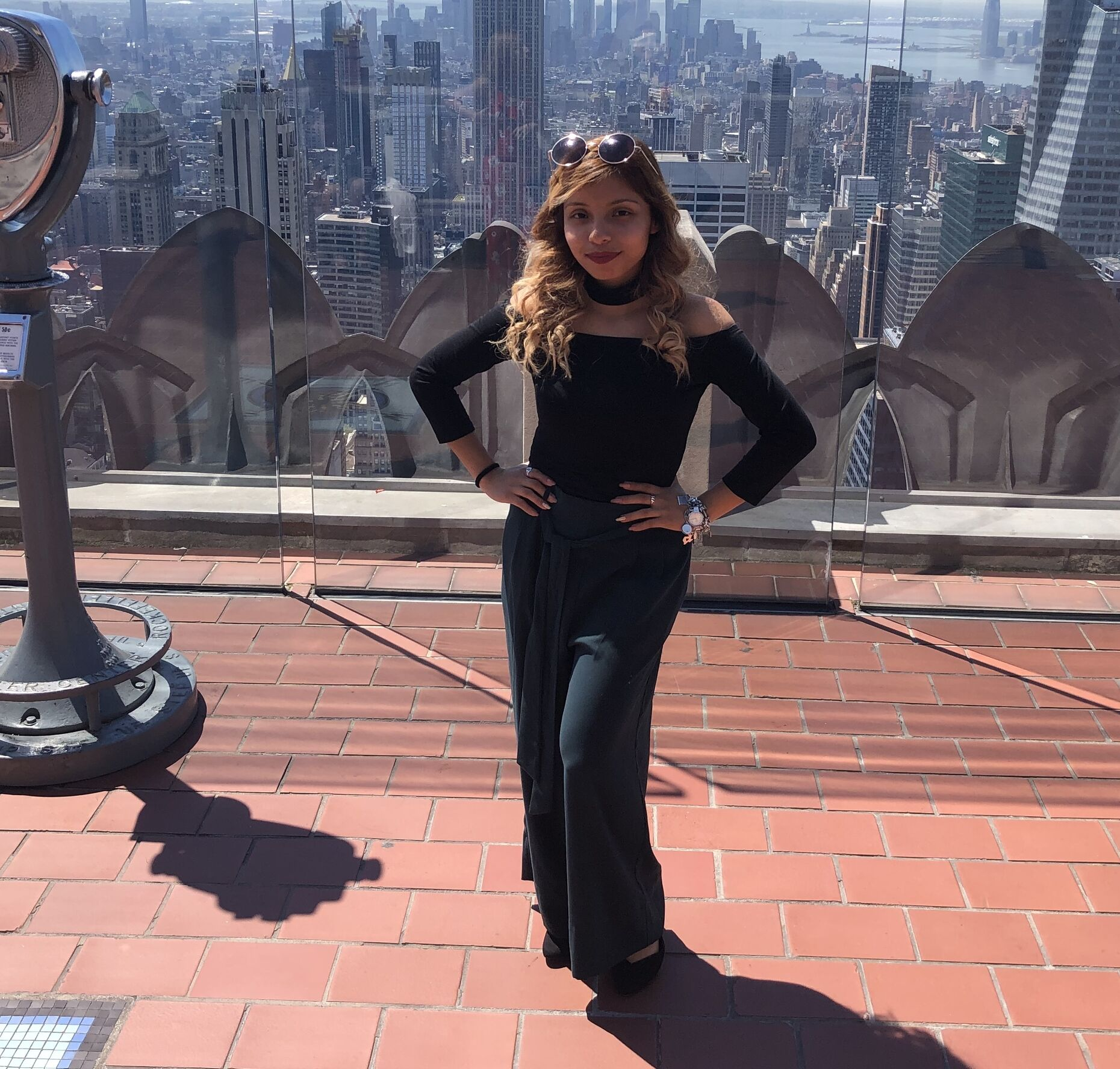 A photo of Maritza standing in front of a city skyline and looking into the camera.