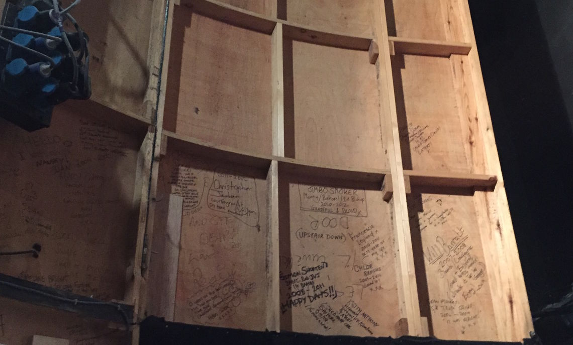 """Behind the sets on the Queen's Theatre stage are signatures from all the actors who have been in the long-running """"Les Misérables."""""""