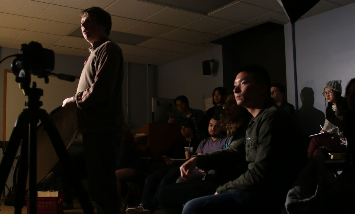 Man standing in front of a camera on a tripod in the middle of a dark classroom full of students.
